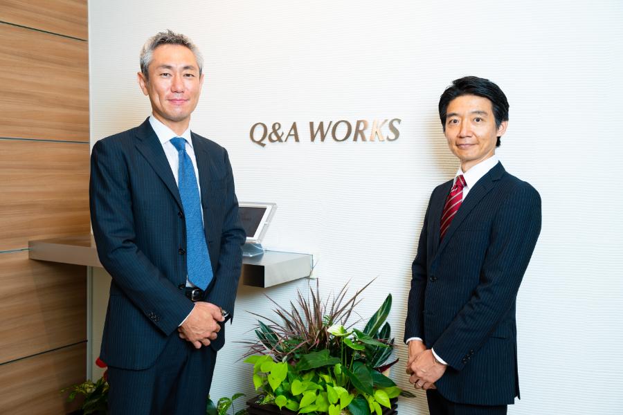キューアンドエーワークス株式会社の代表取締役社長 池邉竜一さんとプロ人材の池辺英治さん、キューアンドエーワークスさんの入り口にて